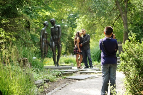 enfant césar prens en photo ses parent devant la statue Adam et Eve